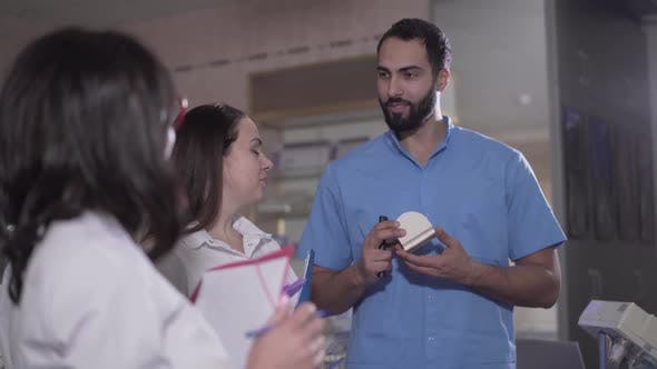 Thumbnail for Portrait of Positive Middle Eastern Male Lecturer Talking To Group of Students About Dentistry