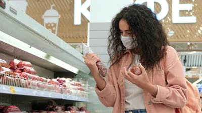 Female Customer with Face Mask is Choosing Sausage in Grocery