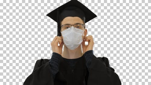 Young man with graduation gown in medical mask, Alpha Channel