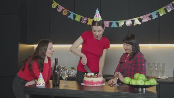 Thumbnail for Happy Woman in Party Hat Cutting Birthday Cake