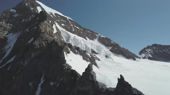 Thumbnail for Mountain Peak in Switzerland Partially Covered in Snow and Smaller Mountains