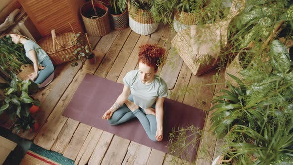 Thumbnail for View from Above of Woman Meditating in Lotus Pose at Home