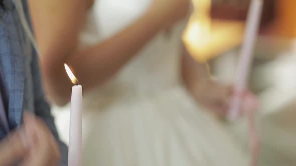 Thumbnail for The Bride and the Groom Stand in Church, Holding Candles in Their Hands