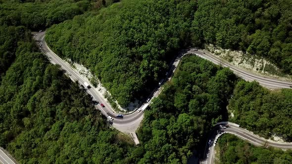 Aerial View of a Curved Winding Road with Cars Passing