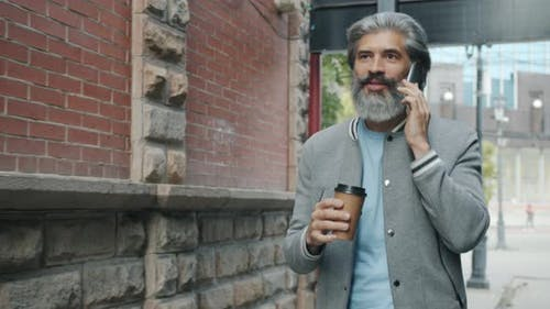 Slow Motion of Handsome Grayhaired Man Chatting on Mobile Phone and Drinking to Go Coffee Walking