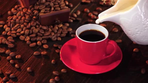 In Little Red Cup of Espresso Poured Milk. Slow Motion