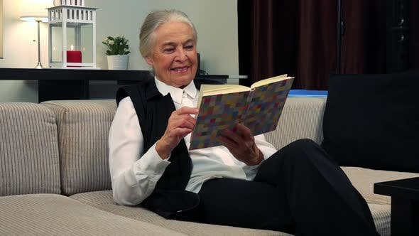 Thumbnail for Old Caucasian Woman Reads a Book in Living Room