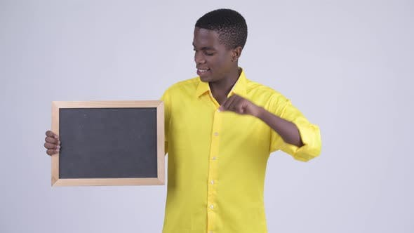 Cover Image for Young Stressed African Businessman Holding Blackboard and Giving Thumbs Down