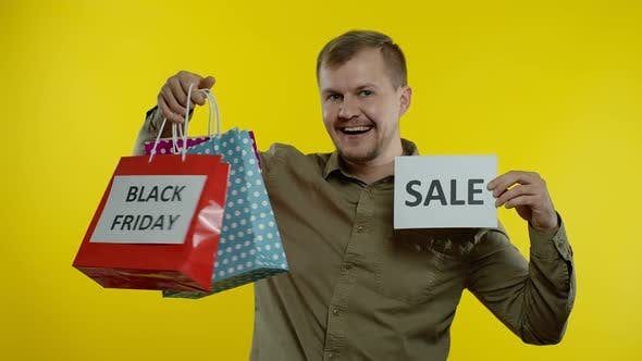 Thumbnail for Happy Smiling Man with Shopping Bags Showing Black Friday Inscription on Bags and Sale Word Note