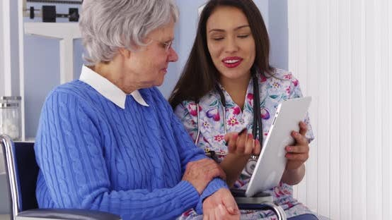 Thumbnail for Mexican caregiver sharing tablet with elderly patient