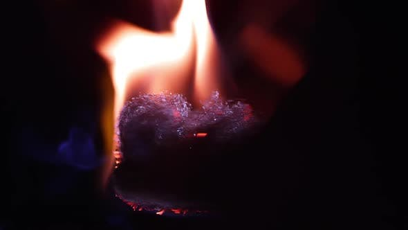 Thumbnail for Fire burning on steel wool as it is spinning while floating.