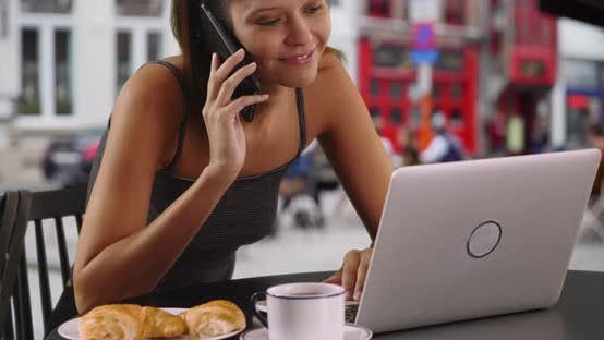 Thumbnail for Female tourist in outdoor cafe with laptop chatting on cellphone
