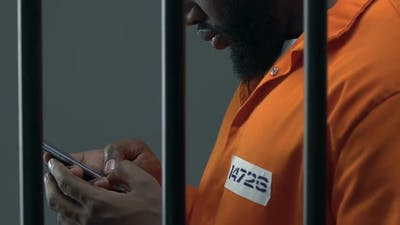 African-American Prisoner Scrolling on Smartphone, Forbidden Items in Jail
