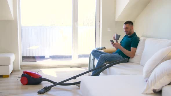 Cover Image for Man with Smartphone and Vacuum Cleaner at Home 28