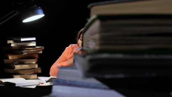 Cover Image for Girl Leafing Through a Book and Falling Asleep at the Table. Black Background