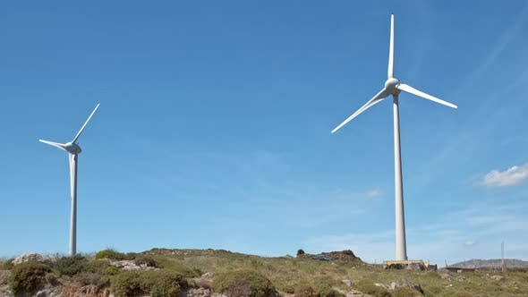 Thumbnail for Diagonal Shot of Two Wind Turbines and Road In-between in Hill Landscape on Sunny Day