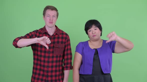 Thumbnail for Sad Young Multi Ethnic Couple Giving Thumbs Down Together