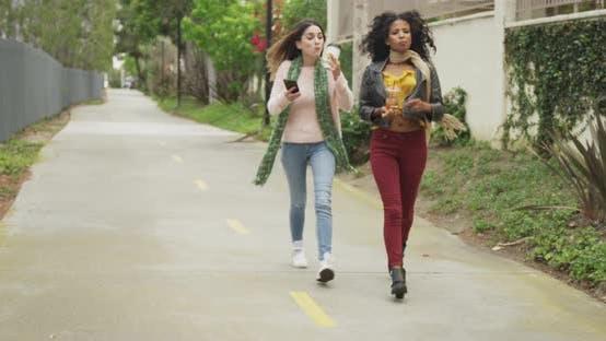 Thumbnail for Stilvolle Frauen, die mit Getränken die Straße hinunter gehen