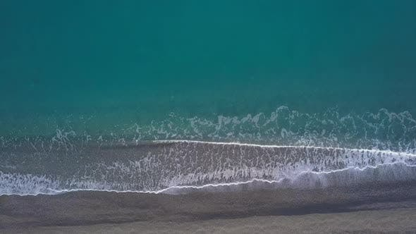 Thumbnail for Top Down View Turquoise Waves Reaching Shore Break on Empty Pebble Beach. Pure Sea From Bird's Eye