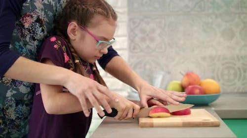 Frau Hilfe Kind zu schneiden Apfelscheibe