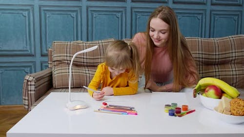 Cute Small Child Kid Daughter Learning Writing Homework with Young Mother Home Distance Education