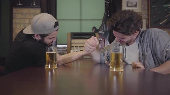 Thumbnail for Zwei Männer sitzen an einem Tisch in einer Bar, engagiert in Armwrestling. Ein Mann gewinnt, der andere verliert