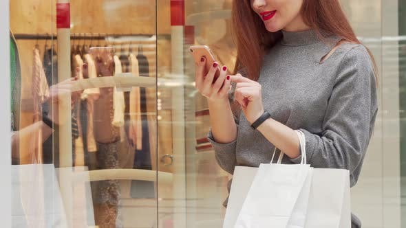 Thumbnail for Woman Smiling, Browsing on Her Smart Phone While Shopping at the Mall