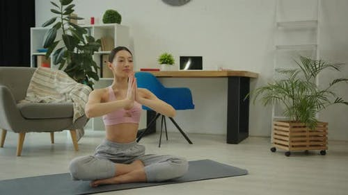 Woman Meditating in Lotus Position and Showing Hand Namaste Gesture at Home