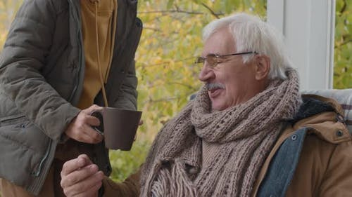 Child Bringing Tea Cup to Grandfather Sitting on Terrace