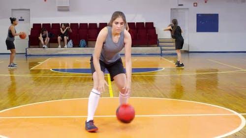 Junge Sportlerin Blick auf die Kamera und Dribbling einen Basketball