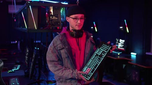 As a Prize a Gamer in a Jacket and Glasses in the Computer Room Received a New Gaming Keyboard and