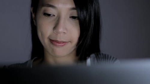 Woman working on laptop computer at night