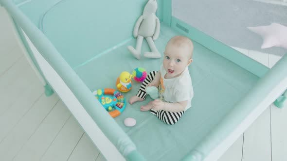 Thumbnail for Cute Baby Girl Playing Toys in Playpen at Home