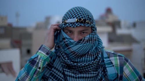 Young Man in Arabic Handkerchief, A Man Looks at the Camera and Covers His Face with a Handkerchief