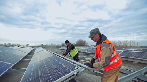 Workers installing photovoltaic solar panels on the roof