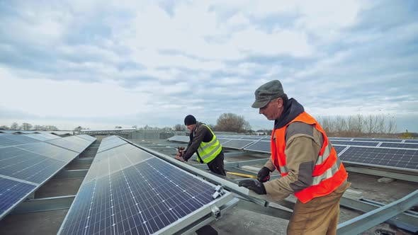 Thumbnail for Workers installing photovoltaic solar panels on the roof