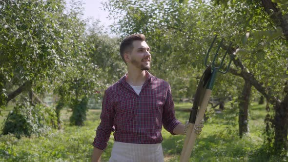 Thumbnail for Young Smiling Bearded Caucasian Farmer Walking Through the Garden with a Spade and Pitchfork