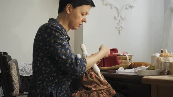 Thumbnail for Seamstress sewing a doll