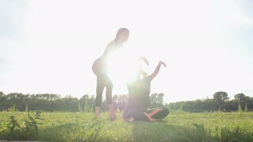 Fitness, Sport, Friendship and Lifestyle Concept - Two Young Women Are Training Stretching Outdoors