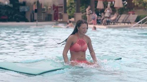 Brunette in Bikini Jumps Up on Swimming Mat Slow Motion