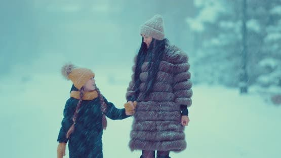 Beautiful Woman in a Fur Coat with a Girl Go in the Winter in the Snowfall Along the Road