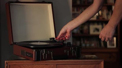 Woman playing Records on Vintage Record Player.