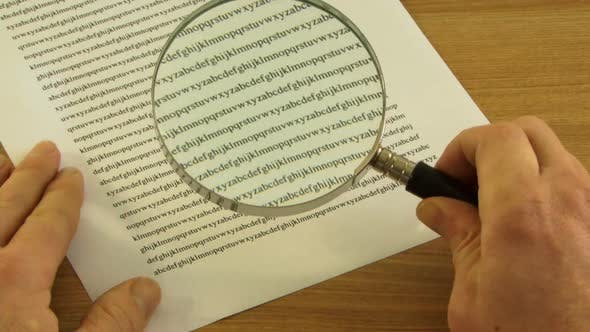 Thumbnail for Looking trough Magnifying Glass at small print in contract