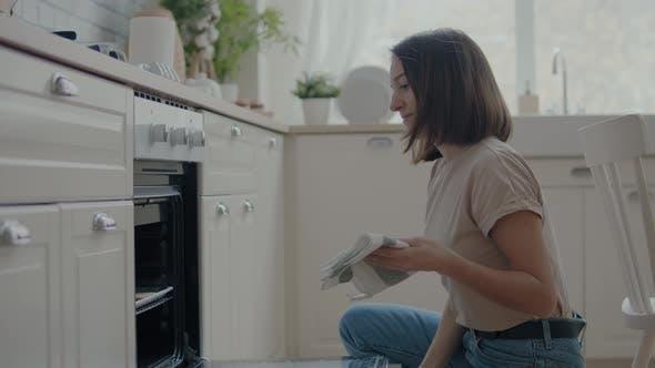 Frau nimmt Plätzchen aus dem Ofen