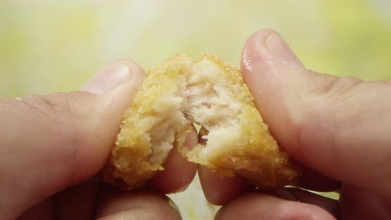 Two Hands Tearing Apart A Piece Of Fried Chicken Nugget On The Table Dollying In To A Macro Shot