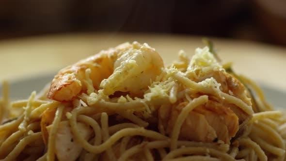 Sprinkling Cheese on Shrimp Pasta