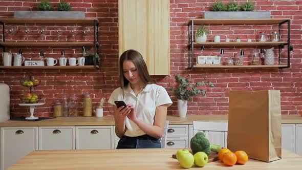 Thumbnail for Woman Browsing on Mobile Phone at Home Kitchen. Young Woman Browsing on Smartphone Smiling Happy.