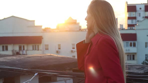 Thumbnail for Woman On A Rooftop Talking On The Phone At Sunset