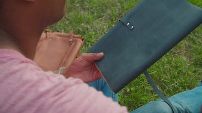 Young Man Opening Leather Sketchbook Sitting on Campus Lawn Outdoors