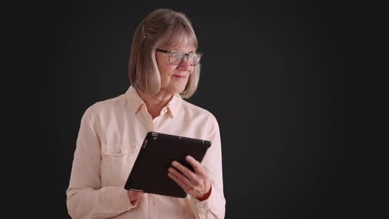 Charming senior woman using tablet device to browse online on gray background